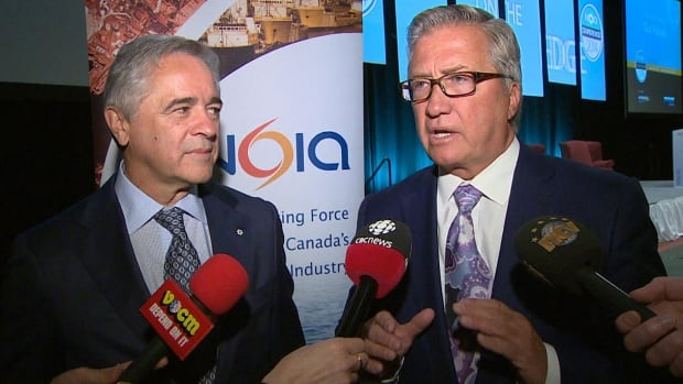 Danny Williams speaks with reporters at the 2014 NOIA conference in St. John's as another former Newfoundland and Labrador premier, Brian Tobin, looks on.
