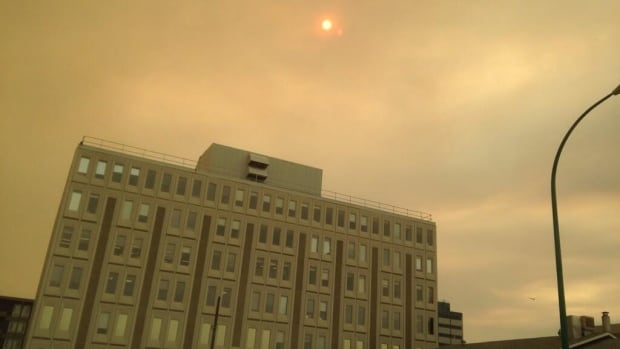 A thick blanket of smoke made Yellowknife skies appear yellow Thursday afternoon. N.W.T.'s Chief Public Health Officer Dr. Andre Corriveau says people who already have lung problems should stay inside with the windows closed when the air outside is smoky.