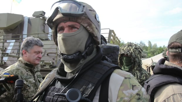 Ukrainian President Petro Poroshenko, background left, inspects a Ukrainian military base close to Slovyansk on Friday. Poroshenko orderedhis forces to cease fire and halt military operations for a week. A day later, Russian President ordered military forces in central Russia on combat alert as well as a drill of airborne troops.