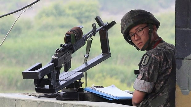 A South Korean soldier stands guard at a military checkpoint near the border with North Korea. A South Korea soldier killed five comrades Saturday night near the border.