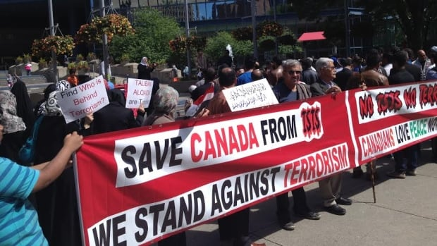 Hundreds of Sunni and Shiite Muslims stood together outside Calgary City Hall Saturday afternoon to protest against the sectarian violence and terrorism ripping apart Iraq.