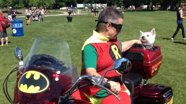 A superhero and her (canine) sidekick hang out at Paws in Motion in Assiniboine Park on Sunday.