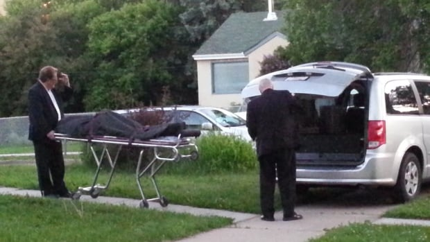 The body of a man is removed from a home at 91st Street and 83rd Avenue on Sunday.