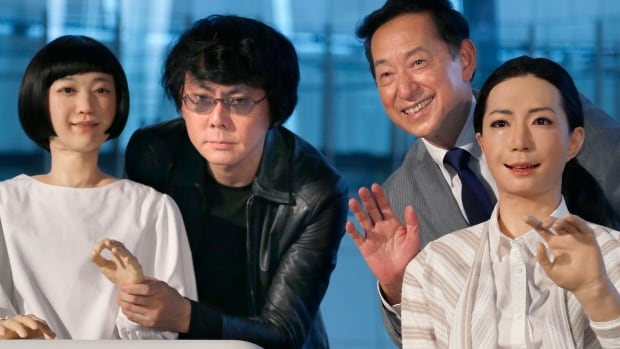 Japanese android expert Hiroshi Ishiguro, second left, and National Museum of Emerging Science and Innovation Miraikan Chief Executive Director Mamoru Mohri, second right, unveiled on Tuesday the museum's new guides: a pair of robots.