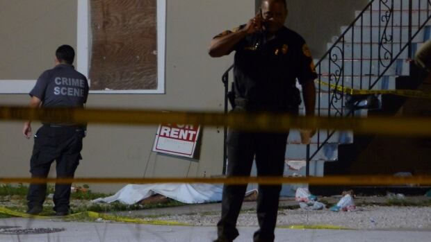 Authorities work the scene where at least two people were killed and multiple others wounded following a shooting early Tuesday in Miami's Liberty City neighbourhood.