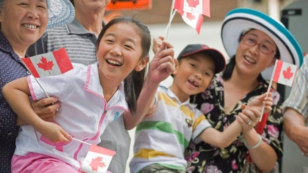 Members of the crowd smile and wave flags as they enjoy the annual Canada Day parade in Montreal. In recent years, fewer immigrants are moving to Montreal.