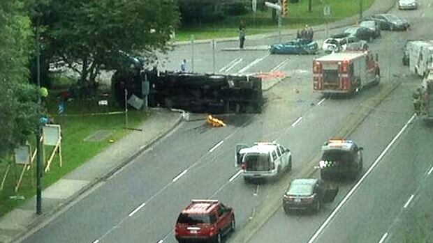 A commercial truck lies on its side in the aftermath of a three vehicle collision that killed an elderly woman riding a mobility scooter in Port Moody Tuesday afternoon.