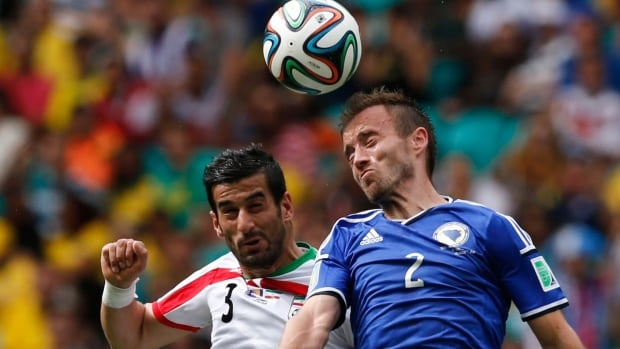 Iran's Ehsan Hajsafi, left, jumps for the ball with Bosnia's Avdija Vrsajevic during Wednesday's FIFA World Cup Group F match at the Fonte Nova arena in Salvador. (Marcos Brindicci/Reuters)