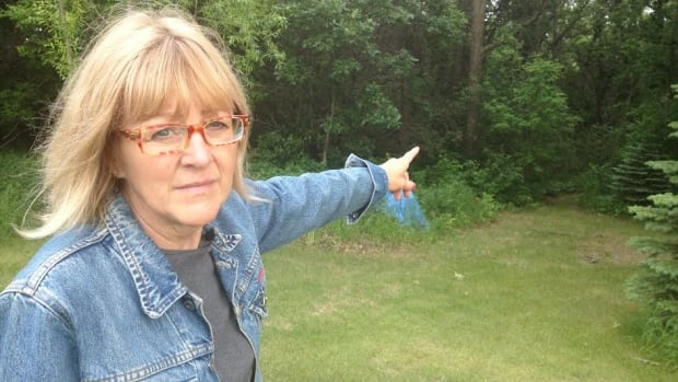 Debbie Molina points to the forest near her house in Stonewall, where she says her dogs were poisoned and she has found the carcasses of wild animals.