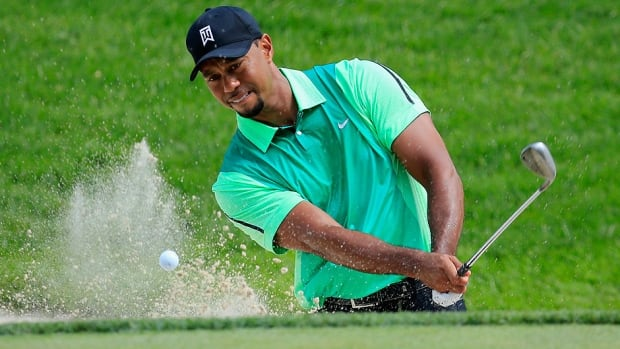 Tiger Woods hits out of the bunker on the third hole during the first round of the Quicken Loans National at Congressional in Bethesda, Md., on Thursday. Woods had seven bogeys in his first 12 holes but settled down to shoot 3-over 74.