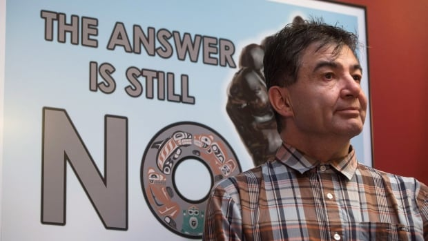 Chief Francis Laceese, of the Tl'esqox First Nation, stands in front of a poster showing opposition to the Enbridge Northern Gateway Pipeline during a news conference following the Supreme Court of Canada ruling in favour of the Tsilhqot'in First Nation.