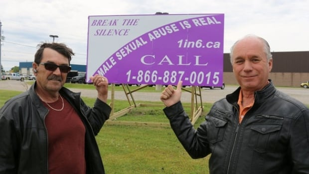 Ray Lariviere and Ray Auclair stand in front of a Timmins sign advertising a phone hotline for male sexual abuse survivors to call.