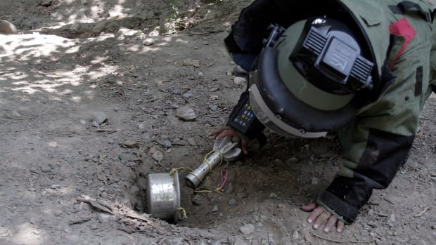 Afghan soldier Ali Raza, 30, searches for landmines with a metal detector in a training exercise. The U.S. announced steps toward banning the use of landmines today.