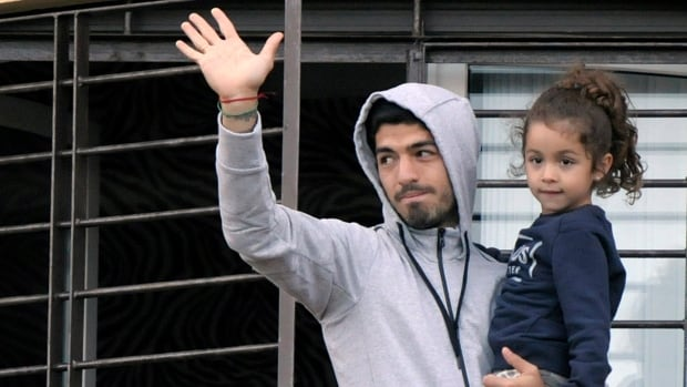 Uruguay's soccer player Luis Suarez holds his daughter as he greets fans from their home's balcony on the outskirts of Montevideo on Friday.