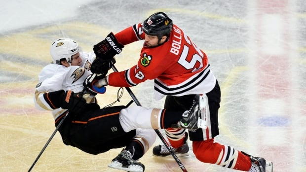 Chicago Blackhawks left wing Brandon Bollig, right, takes out Anaheim Ducks defenseman Ben Lovejoy during a Dec. 6, 2013 game.
