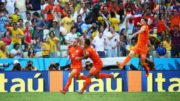 Wesley Sneijder of the Netherlands, left, celebrates scoring the tying goal in the 88th minute for the Netherlands against Mexico in the teams; Round of 16 match at the 2014 FIFA World Cup.