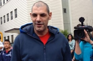Gino Odjick greets cheering fans outside the hospital