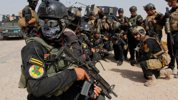 Members of the Iraqi Special Operations Forces prepare before going out on a patrol south of Baghdad. Iraqi troops battled to dislodge an al-Qaeda splinter group from the city of Tikrit on Monday after its leader was declared caliph of a new Islamic state.