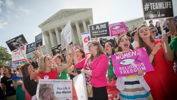 Demonstrator cheer Monday's decision on what has become known as the Hobby Lobby case, outside the U.S. Supreme Court in Washington.