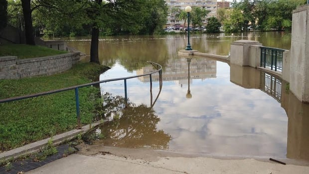 The Assiniboine River is so swollen from rainfall that it is far above the walking path near the legislative building.