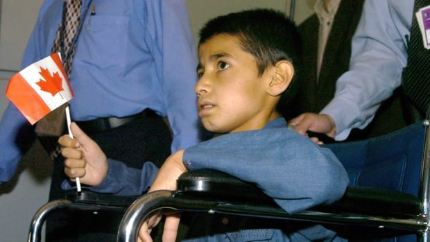 Djamshid Popal is wheeled to a vehicle after arriving at Pearson International Airport in Toronto Friday July 2, 2004.