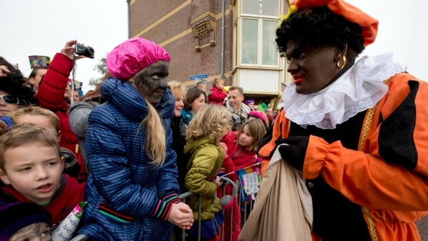 Children, some with faces painted black, wait for Black Peter, right, to hand them candy in Hoorn, north-western Netherlands on Nov. 16, 2013. Supporters say Pete is a figure of fun whose appearance is harmless, his face soot-stained from going down chimneys to deliver present for the children.