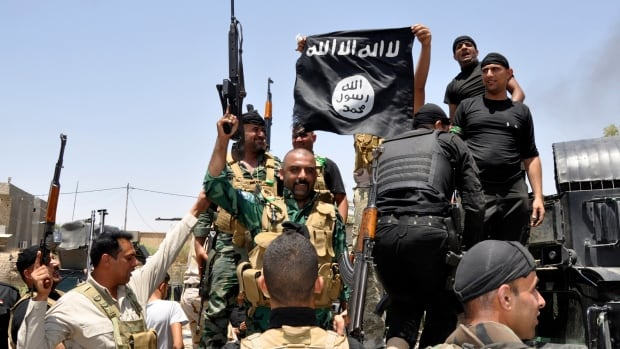 Iraqi security forces pull down a flag belonging to the Islamic State militant group. It was revealed today that the group is holding an American woman hostage, reportedly seeking a $6.6 million US ransom.
