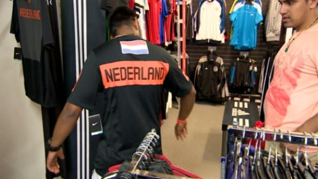 A man tries on a soccer jersey at Eurosport in north Edmonton.