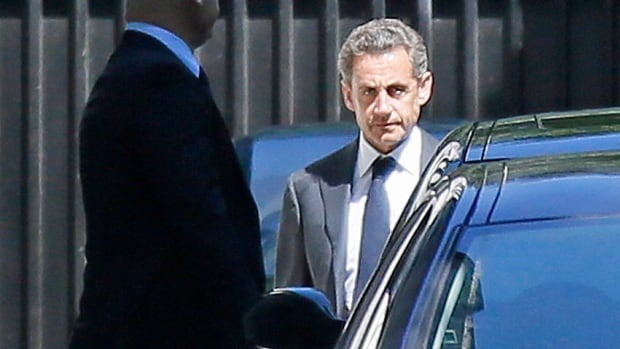 A clearly angered, former French president Nicolas Sarkozy leaves his Paris residence on Wednesday for 15 hours of formal investigation at a police station.