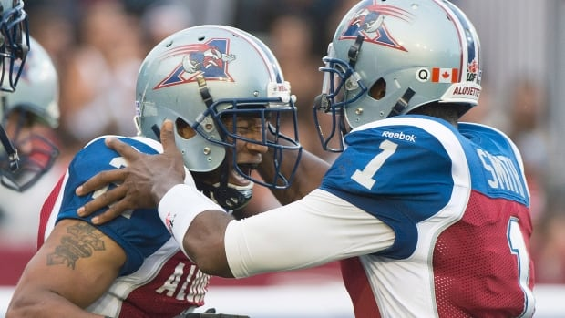 Montreal's Brandon Whitaker celebrates with quarterback Troy Smith, right, after scoring a touchdown against the B.C. Lions during first half CFL football action on Friday.