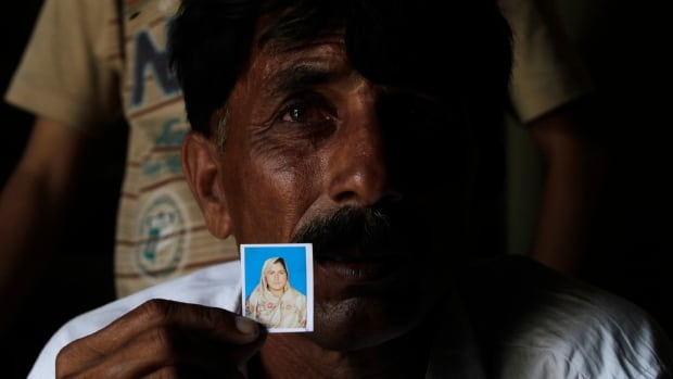 Muhammed Iqbal, 45, shows a picture of his late wife Farzana who was stoned to death. A Pakistani court has charged Farzana's father, two brothers, a cousin and another man with murder and torture.