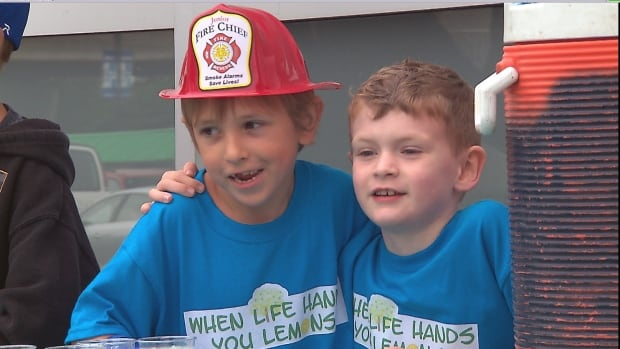 "Brayden Grozdanich and Quinn Callender man their lemonade stand outside a grocery store on Sunday sporting, ""when life hands you lemons..."" T-shirts."