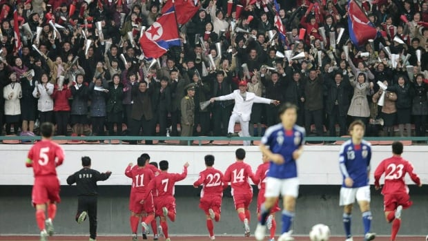 North Korean players run toward the cheering spectators at the stand after beating Japan 1-0 in their 2014 World Cup qualifying soccer match at Kim Il-sung Stadium in Pyongyang, North Korea, in November 2011.