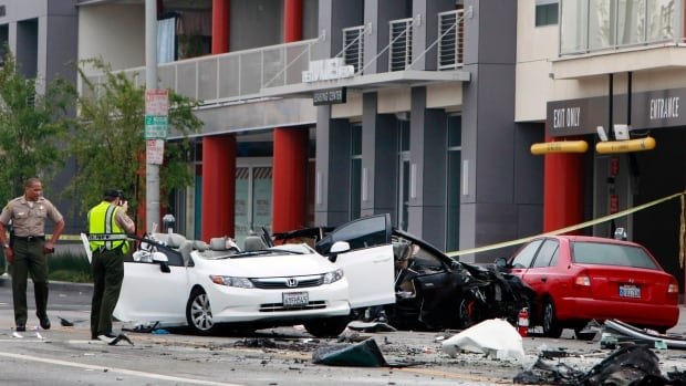 A Los Angeles County sheriff's deputy photographs the remains of a Tesla in West Hollywood, Calif. on Friday, July 4, 2014. The black Model S split in two after hitting a lamppost. The other half is wedged in a building across the street.