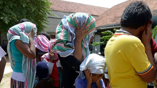 Asylum seekers who were sent back to Sri Lanka by Australia cover their faces as they wait to enter a magistrate's court in Galle. High Court Justice Susan Crennan issued a temporary injunction late Monday night halting any further transfers.