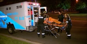 Paramedics load an injured victim into the back of an ambulance after a shooting early Tuesday morni