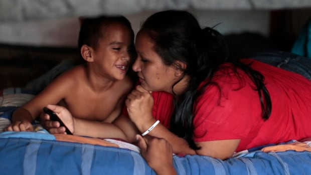 Honduran citizen Brenda Maribel Perdomo listens to her son Jefferson at the Todo por ellos (All for them) immigrant shelter in Tapachula, Chiapas, in southern Mexico.In the past year, some 52,000 children were detained at the U.S. border with Mexico, most of them from Central America.