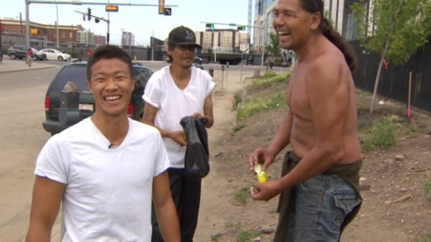 Mathew Wong (left), a registered nurse with Boyle Street Community Services, enjoys a laugh with a man after giving him a container of sunscreen.