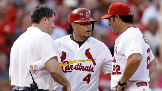 St. Louis Cardinals' Yadier Molina, centre, is checked on by manager Mike Matheny, right, and trainer Chris Conroy after injuring his hand while sliding into third on Wednesday against the Pirates. Molina tore a ligament in his right thumb and will be sidelined for the next 8-12 weeks.