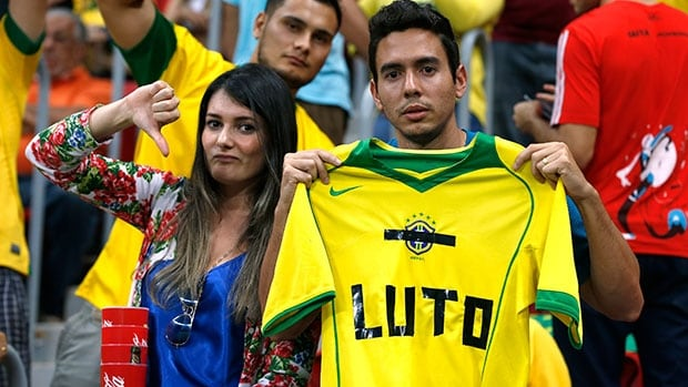 "Fans hold up a Brazil jersey reading, ""Mourn"" during the 2014 World Cup third-place loss to the Netherlands on Saturday at Brasilia national stadium."