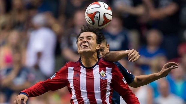 Chivas USA's Erick Torres gets his head on the ball while being challenged by the Whitecaps' Johnny Leveron, back, in the second half on Saturday night. Chivas won the game 3-1.