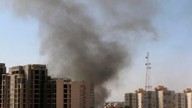 Smoke rises near buildings after heavy fighting between rival militias broke out near the airport in Tripoli, forcing the suspension of all flights.
