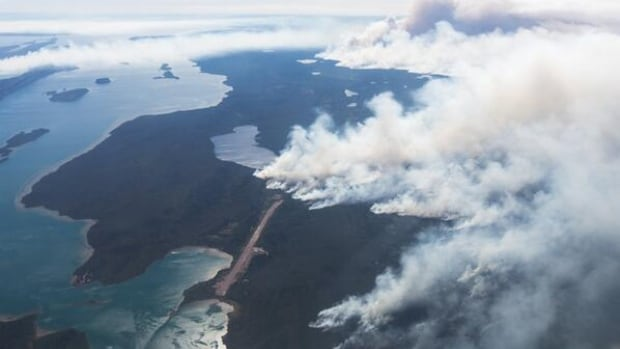 Fire approaches Plummer's Lodge on the East Arm of Great Slave Lake July 12. The lodge survived after firefighters initiated a controlled burn.