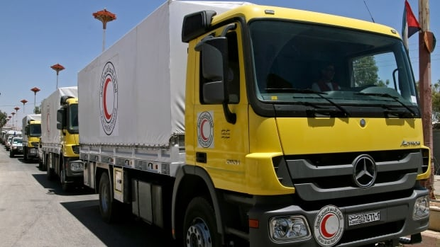 Some 13 Syrian Red Crescent trucks loaded with 1,000 food parcels under the supervision of the UN, the Red Crescent and in co-ordination with the Syrian government, prepare to distribute aid to tens of thousands of besieged Syrians inside the rebel-held Damascus suburb of Moadamiyeh, Syria, Monday.