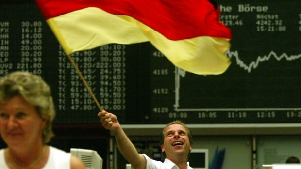 A German stock trader waves a German flag after a German goal in the World Cup. Historically, World Cup winners see gains on their stock market for the next month.