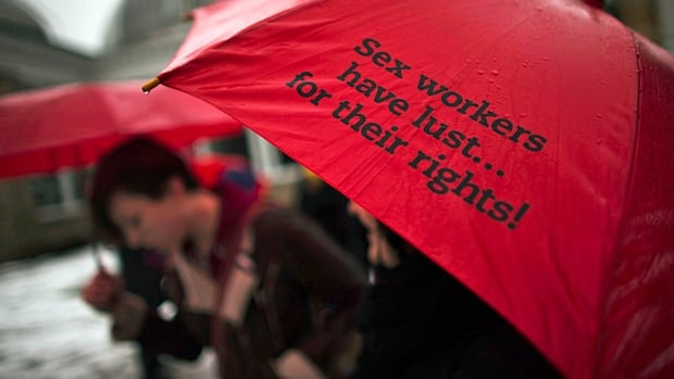 A woman holds a red umbrella, a symbol for sex workers rights, during a 2013 rally in Toronto as the Supreme Court struck down Canada's prostitution laws in a unanimous 9-0 ruling. Senators will hear testimony on the government's replacement bill this week.