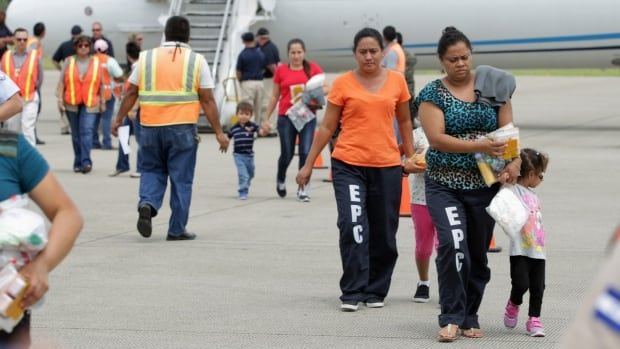 Women and their children walk on the tarmac after being deported from the U.S. The U.S. deported a group of Honduran children on Monday in the first flight since President Barack Obama pledged to speed up the process of sending back illegal immigrant children from Central America.