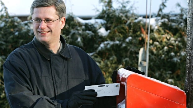 Prime Minister Stephen Harper is shown using a Canada Post box in 2005. This year, the party's patriotism-themed mail-outs are raising eyebrows in some ridings.