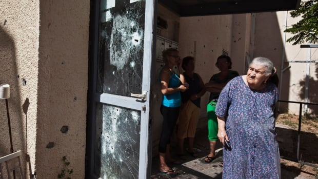 Israeli women stand near a building damaged after by Palestinian militant rocket fire. Israel is intensifying its week-old offensive against Hamas after the Islamist group continued firing rockets at Israel instead of accepting an Egyptian-proposed ceasefire.