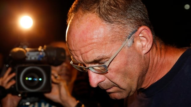 Douglas Garland is escorted into a Calgary police station in connection with the disappearance of Nathan O'Brien and his grandparents in Calgary Monday.